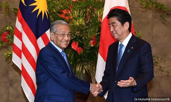 资料图:马来西亚总理马哈蒂尔(左)与日本首相安倍晋三